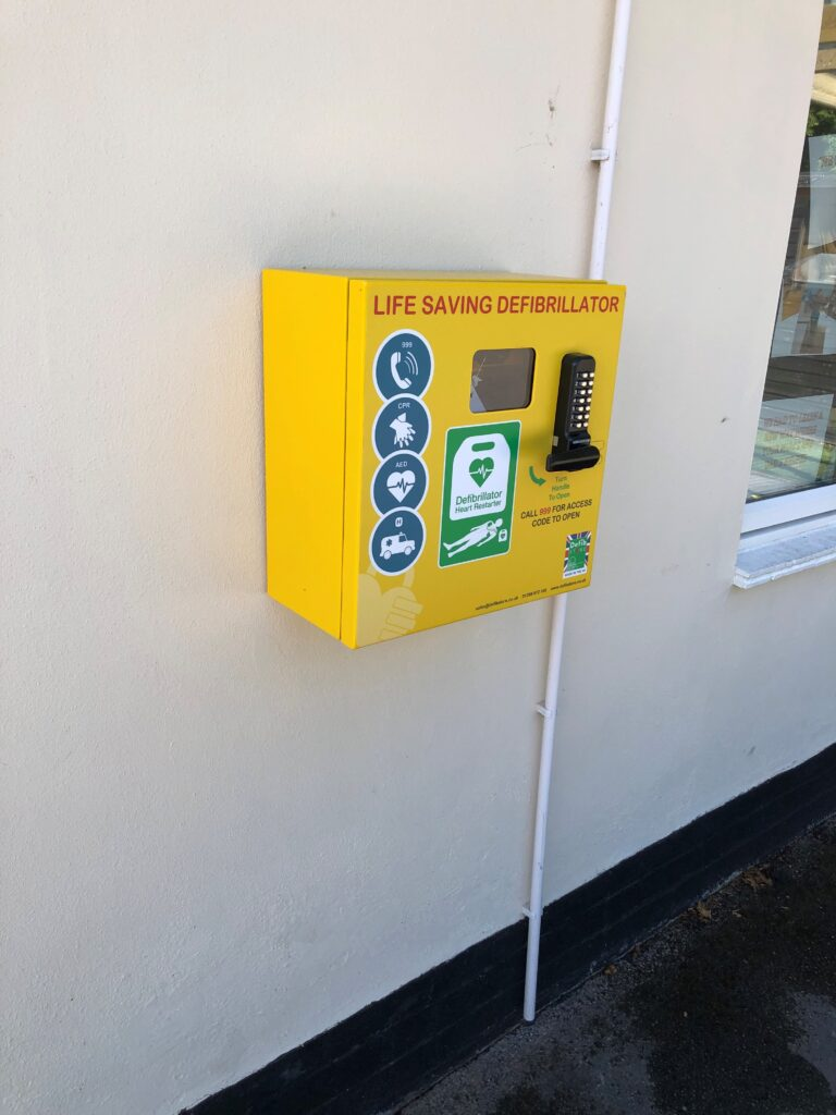 Yellow defibrillator on wall of Hollies nursery